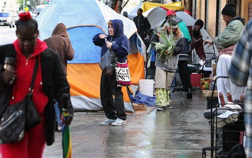 Skid Row residents start their morning, Monday, March 2, 2015, on a street near where a man was shot and killed by police on Sunday, in downtown Los Angeles. Three Los Angeles police officers shot and killed the man as they wrestled with him on...