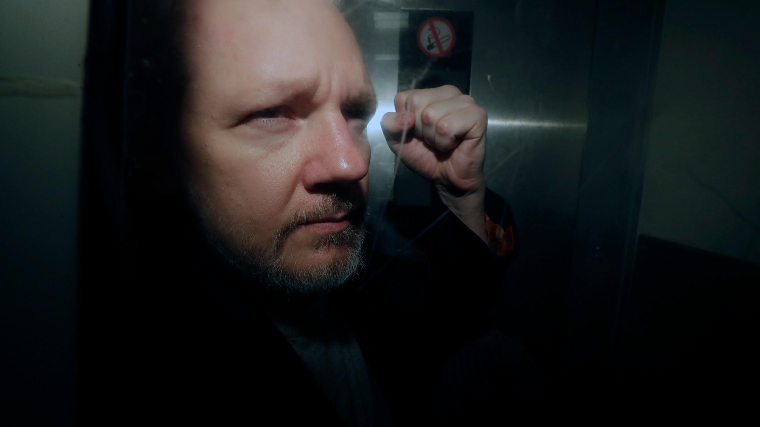 WikiLeaks founder Julian Assange puts his fist up as he is taken from court in London