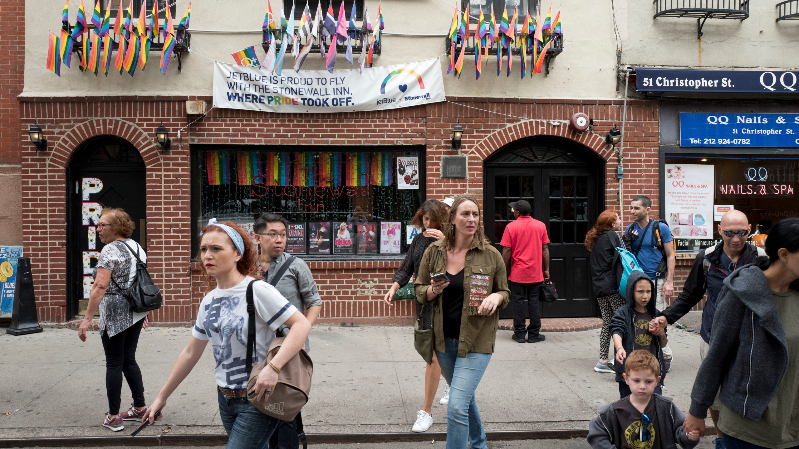 People pass the Stonewall Inn, in New York City's West Village.