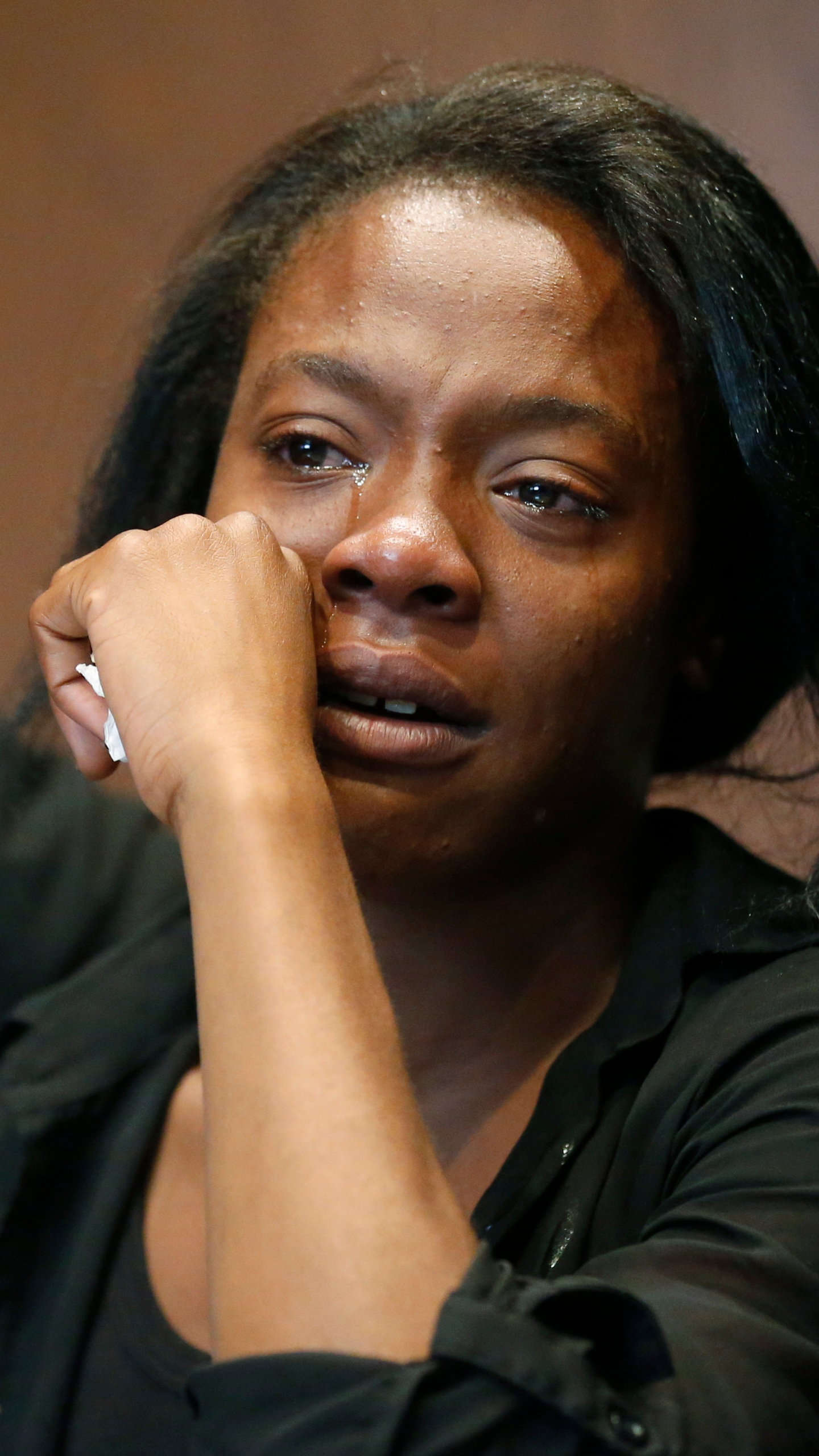Olivia Hill wipes away tears as she speaks